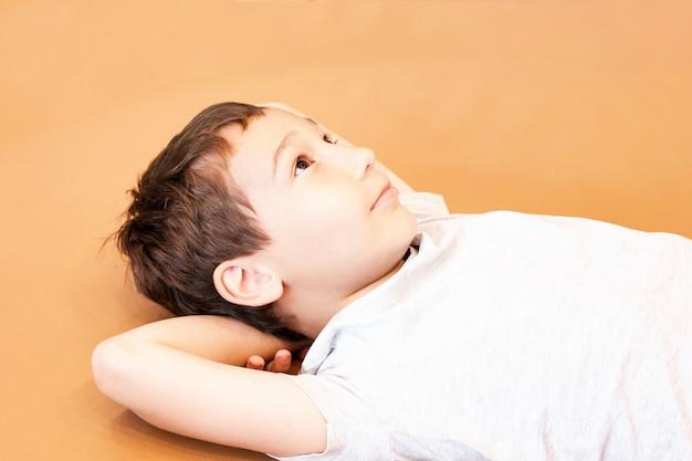 Un garçon de 8 ans ment et rêve sur un fond orange