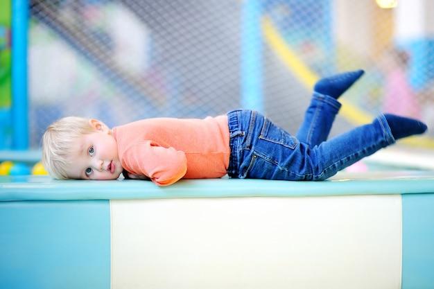 Garçon actif bambin jouant à l'aire de jeux intérieure