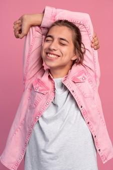 Garçon de l'adolescence élégant en posant rose