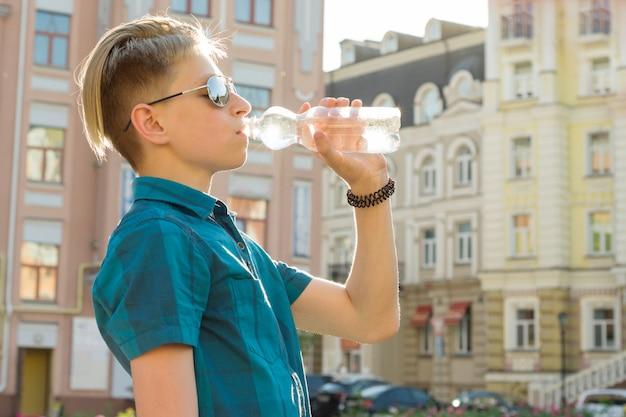 Garçon adolescent boit de l'eau de bouteille