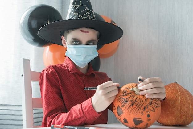 Garçon adolescent en costume se préparant pour la célébration d'halloween dessinant une citrouille. carnaval d'halloween avec une nouvelle réalité avec le concept de pandémie