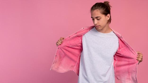 Garçon adolescent élégant en rose posant avec espace de copie