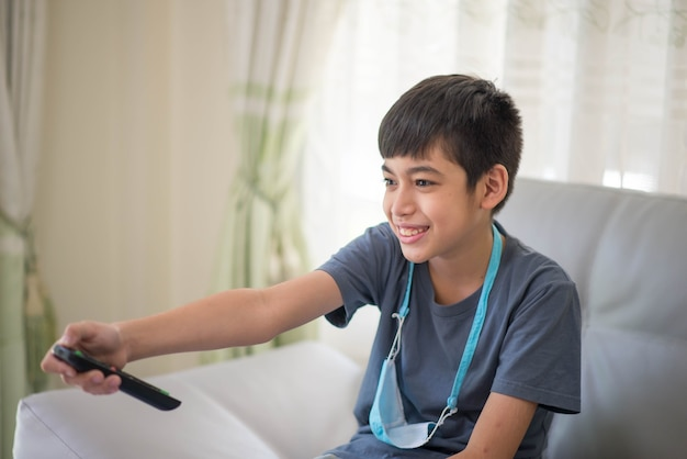 Garçon adolescent enfant prendre la télécommande en main regarder la télévision