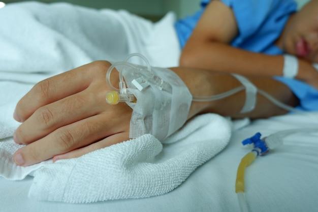 Un garçon adolescent était malade et dormait avec une solution saline intraveineuse à l'hôpital