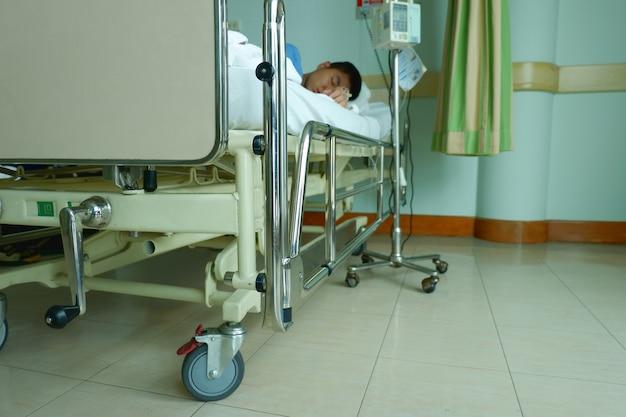 Le garçon d'adolescent était malade et dors avec l'équipement iv tube de pompe d'infusion à l'hôpital