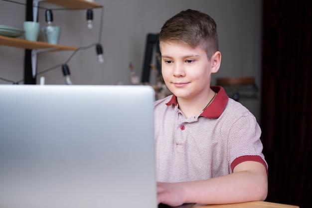Garçon adolescent étudiant en ligne, jouant à des jeux vidéo à l'aide d'un ordinateur portable assis sur la cuisine.