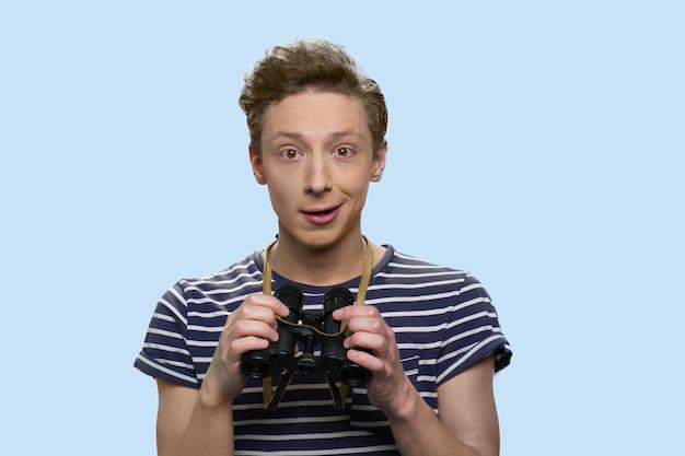 Garçon adolescent excité avec des jumelles. isolé sur fond bleu. beau garçon caucasien souriant en t-shirt rayé.