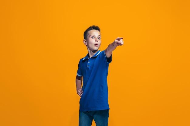 Le garçon adolescent heureux pointant vers vous, portrait gros plan demi-longueur sur fond orange.