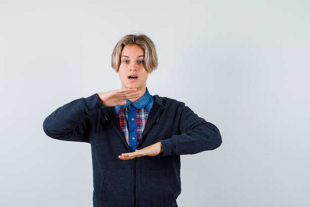 Garçon adolescent mignon montrant le signe de la taille dans la chemise, le sweat à capuche et l'air étonné, vue de face.