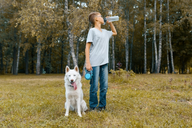 Garçon adolescent propriétaire d'un chien blanc husky eau potable