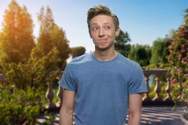 Garçon adolescent songeur rêveur. garçon américain adolescent en t-shirt gris. terrasse d'été verdoyante en arrière-plan.