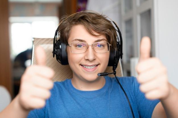 Garçon adolescent souriant dans les écouteurs avec microphone garde les pouces vers le haut diring appel vidéo en ligne.