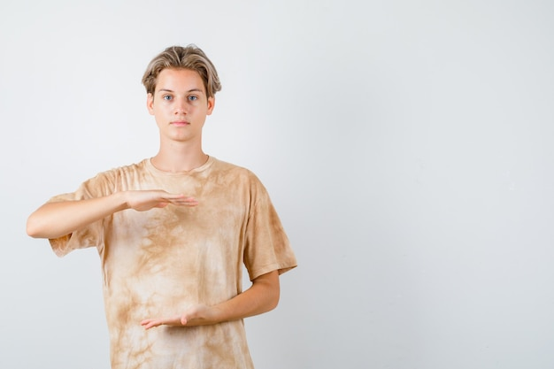 Garçon adolescent en t-shirt montrant un signe de grande taille et l'air confiant, vue de face.