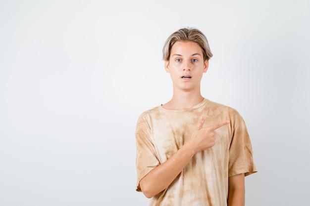 Garçon adolescent en t-shirt pointant vers le coin supérieur droit et se demandant , vue de face.