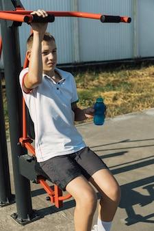 Garçon adolescents travaillant sur le terrain de sport de l'eau potable de la bouteille thermos.