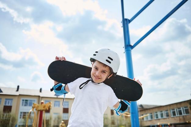 Garçon adorable dans un casque de protection et un équipement posant avec une planche à roulettes sur ses épaules derrière sa tête