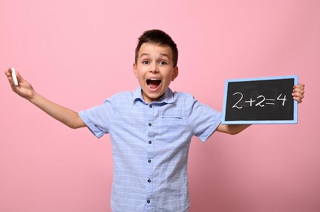 Un garçon adorable, un élève du primaire, tient une craie et un tableau et résout avec bonheur des problèmes de mathématiques. fond rose pour le texte