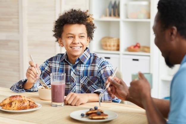 Garçon africain aux cheveux bouclés souriant à son père pendant qu'ils prennent leur petit déjeuner ensemble dans la cuisine