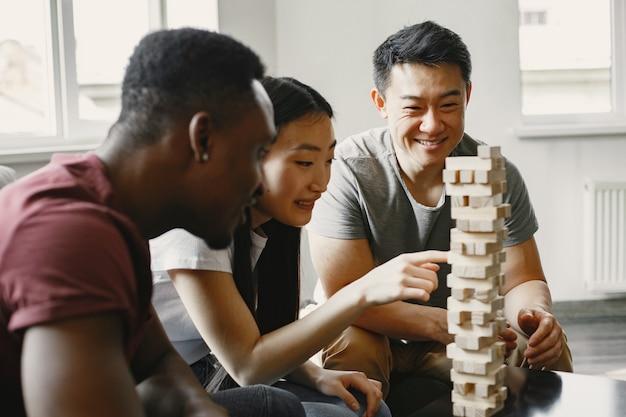 Garçon africain et couple asiatique jouant au jenga jouer à un jeu de société pendant un temps libre