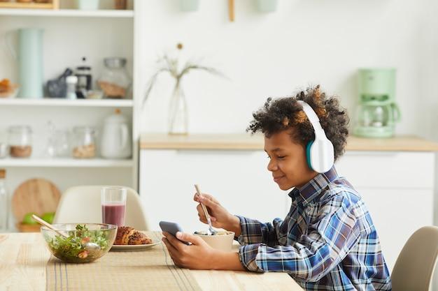 Garçon africain dans les écouteurs à l'aide de son téléphone portable tout en mangeant le petit déjeuner dans la cuisine