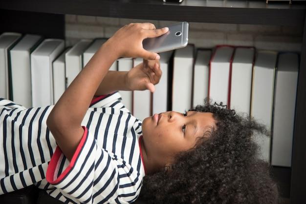 Garçon africain noir, jouer au téléphone portable à l'école.