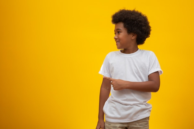 Garçon afro-américain aux cheveux noir sur jaune. enfant noir souriant avec un cheveu noir. garçon noir avec des cheveux noirs. descendance africaine.