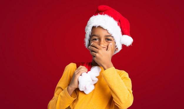 Garçon afro-américain avec un chapeau de noël sur fond rouge