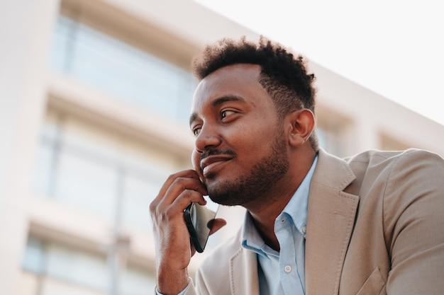 Garçon afro-américain en costume parlant sur un téléphone intelligent avec un client de son entreprise dans un endroit où l'on voit les bâtiments de l'entreprise. plan fermé.