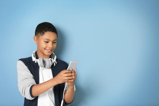 Garçon afro-américain avec des écouteurs sur bleu