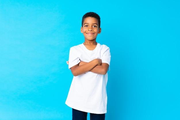 Garçon afro-américain isolé bleu souriant beaucoup