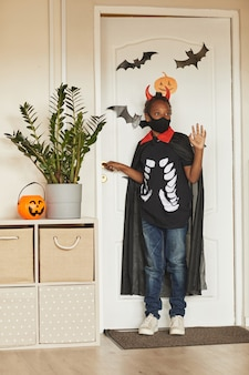 Garçon afro-américain méconnaissable portant un costume de diable avec des cornes rouges et un masque noir sur le visage disant au revoir à ses parents et va tromper ou traiter.