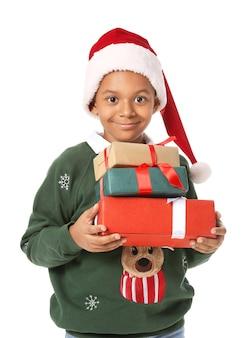Garçon afro-américain mignon en bonnet de noel et avec des cadeaux de noël sur blanc