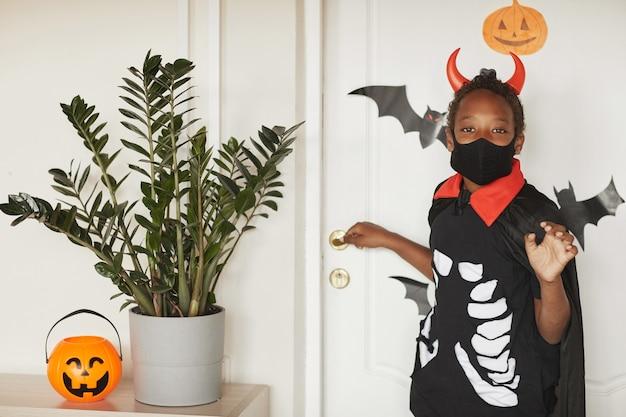 Garçon afro-américain moderne portant un costume de diable avec des cornes rouges et un masque noir sur le visage disant au revoir à ses parents et va tromper ou traiter avec des amis.