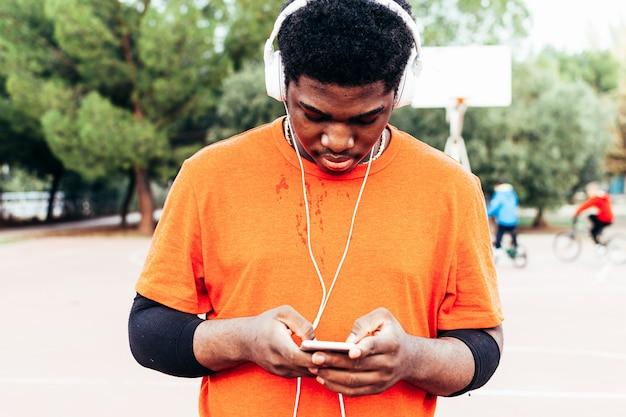 Garçon afro-américain noir écoutant de la musique avec des écouteurs et son téléphone portable après avoir joué au basket-ball sur un terrain urbain. habillé d'un t-shirt orange.