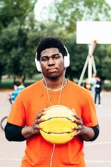 Garçon afro-américain noir écoutant de la musique avec des écouteurs et son téléphone portable après avoir joué au basket-ball sur un terrain urbain.