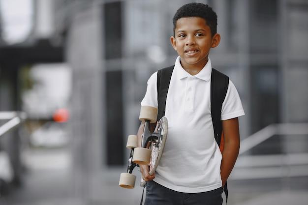 Garçon afro-américain avec planche à roulettes