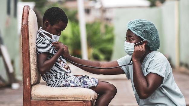 Garçon afro-américain se faire examiner par un médecin