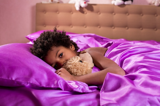 Garçon afro avec ours en peluche. garçon au lit avec ours en peluche. regard fatigué de ses yeux. il est temps de glisser.