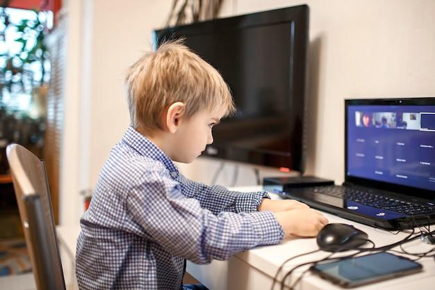 Garçon d'âge préscolaire étudie pendant la leçon en ligne à la maison