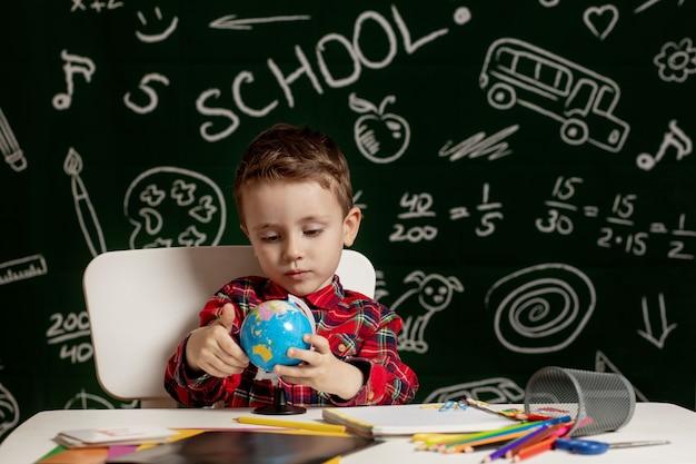 Garçon d'âge préscolaire à faire ses devoirs. écolier avec une expression de visage heureux près du bureau avec des fournitures scolaires. éducation. l'éducation en premier. notion d'école.