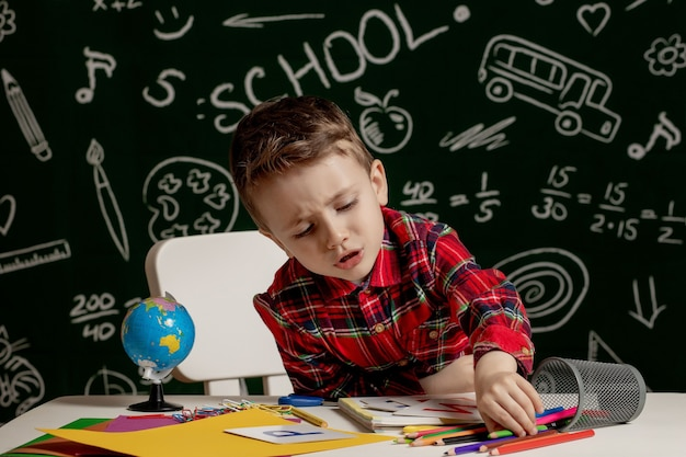 Garçon d'âge préscolaire, faire ses devoirs scolaires