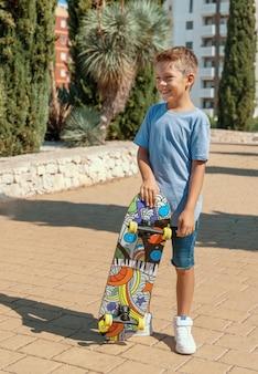Garçon d'âge préscolaire en t-shirt reste avec une planche à roulettes dans un parc. maquette de chemise