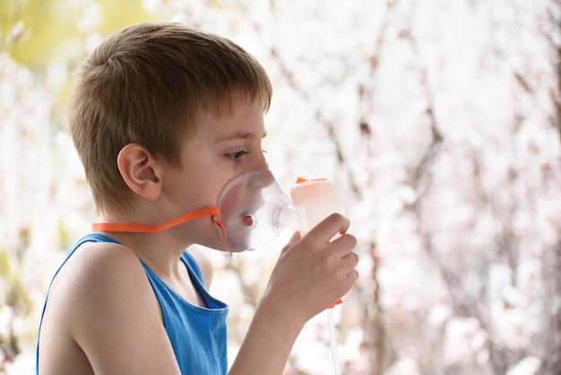 Un garçon d'âge scolaire fait l'inhalation à la maison. la prévention