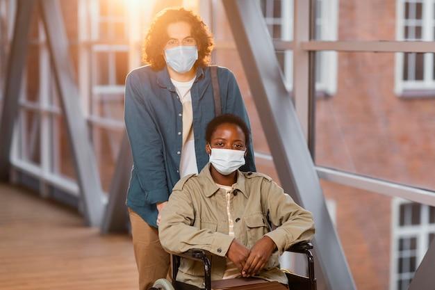 Garçon aidant son collègue en fauteuil roulant à aller en classe