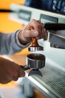 Garçon à l'aide d'un pilon pour presser le café moulu dans un porte-filtre