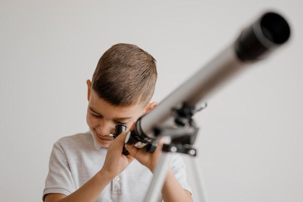 Garçon à l'aide d'un télescope en classe
