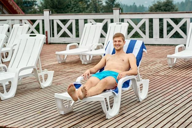 Garçon allongé sur une chaise de plage avec une serviette à rayures bleues.