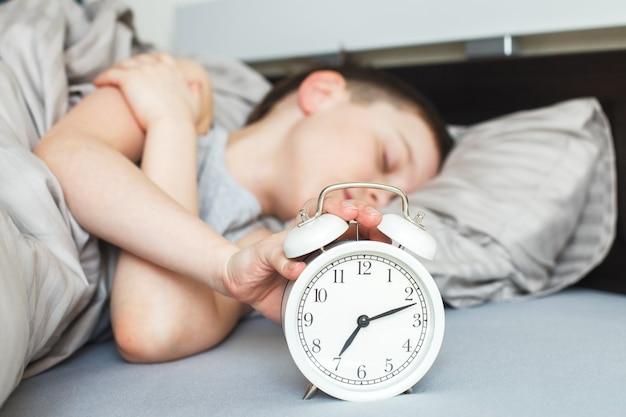 Garçon allongé sur le lit et arrêtant le réveil