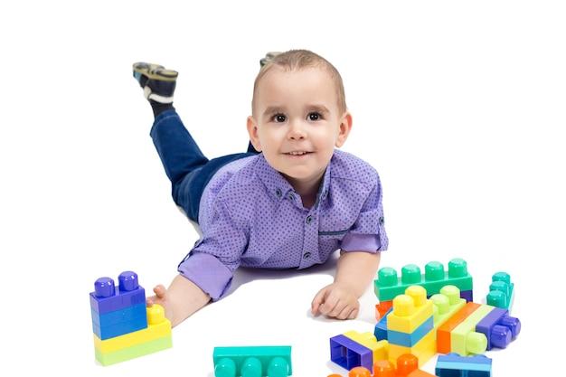 Garçon allongé sur le sol avec des jouets, fond blanc isolé