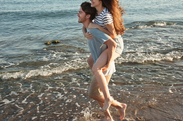 Garçon ami qui porte une petite amie au rivage